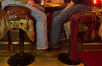 Matt Williams, left, of Jackson, and Amy Harmer, of Ennis, Mont., sit atop bar stolls made of saddles at the Million Dollar Cowboy Bar on the town square in Jackson, Wyo. (Kevin Moloney for the New York Times)