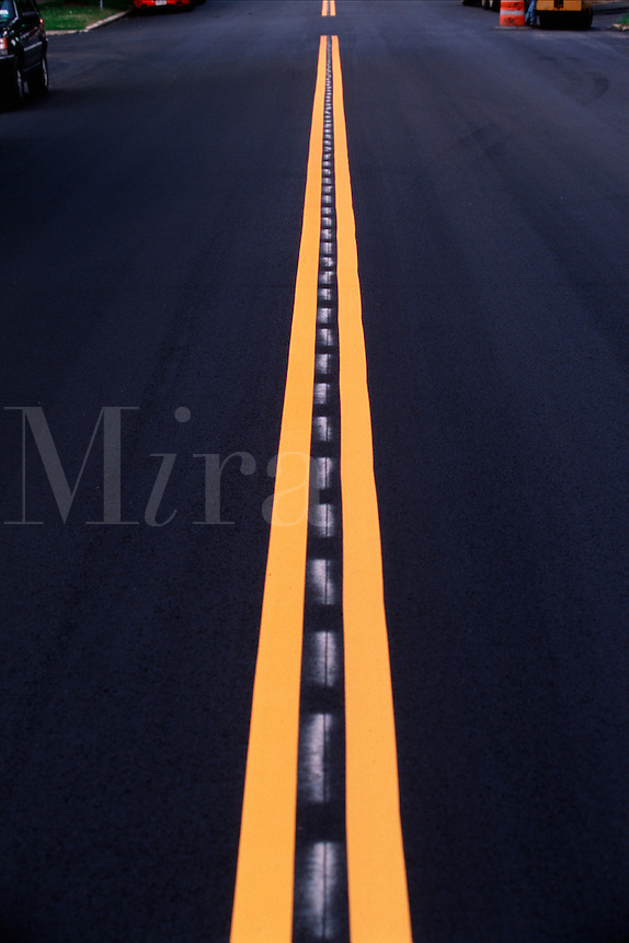 Yellow center lines on a freshly paved road.