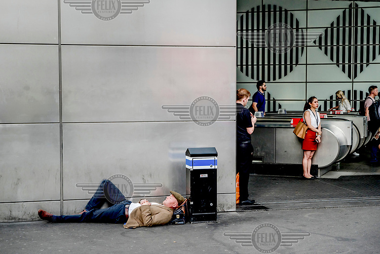 A man sleeps outside Tottenham Court Road Station in the early morning.