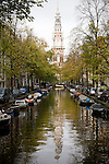 The canal along the Groeneburgwal in Amsterdam with the Zuiderkerk reflected in the water.