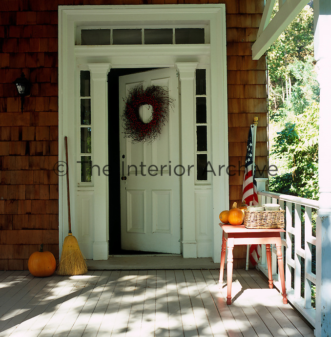 A wreath hangs on the open front door of a shingled house