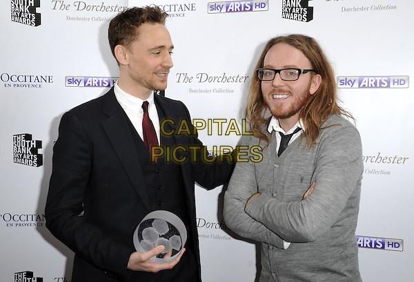 Tom Hiddleston ( Times Breakthrough Award winner ) & Tim Minchin.attended the South Bank Sky Arts Awards 2013, Dorchester Hotel, Park Lane, London, England..March 12th, 2013.half length black grey gray white suit shirt beard facial hair cardigan award trophy winner glasses profile arms crossed.CAP/ROS.©Steve Ross/Capital Pictures