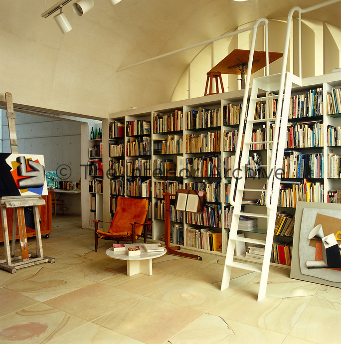 The studio/office is lined with shelves of books above which a small reading area is accessed by a metal ladder