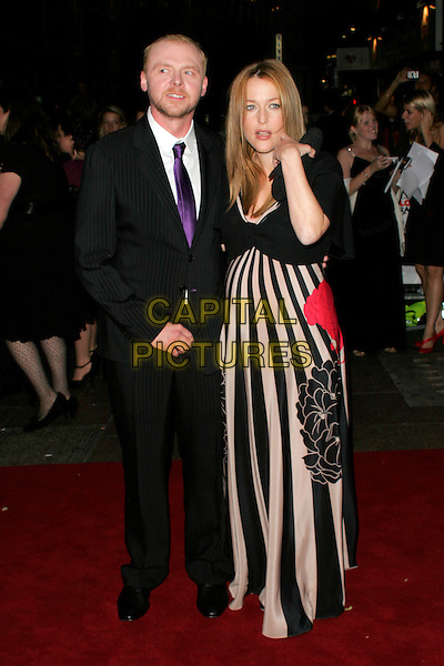 "SIMON PEGG & GILLIAN ANDERSON .World Premiere of ""How to Lose Friends and Alienate People"" at the Empire, Leicester Square, London, England..September 24th 2008.full length black beige striped stripes maxi dress cardigan pregnant red floral print clutch bag pinstripe suit purple tie hand.CAP/AH.©Adam Houghton/Capital Pictures."