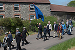 Priddy Friendly Society annual Club Walk Day. Somerset Uk 2019. Members walk around the village behind the Weston Sea Cadets silver band from Weston-super-Mare and the clubs two banners. The oldest banner is solid blue on both sides, while a more recent banner say,  Priddy Friendly Society 1883.