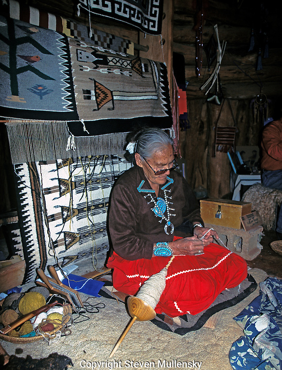 Old Navajo woman, from the Navajo Reservation at Monument Valley, Utah, sits in her hogan and spins wool from her sheep to use for weaving rugs like those behind her.