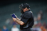 Home plate umpire Wes Hamilton makes notes during the NCAA baseball game between the Missouri Tigers and the Texas Longhorns in game eight of the 2020 Shriners Hospitals for Children College Classic at Minute Maid Park on March 1, 2020 in Houston, Texas. The Tigers defeated the Longhorns 9-8. (Brian Westerholt/Four Seam Images)