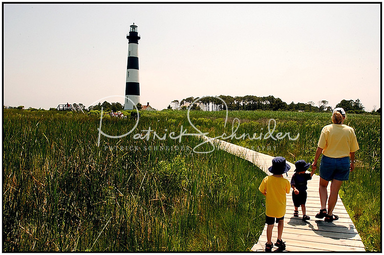 A family walks along the wooden boardwalk at Bodie Island Light House in the North Carolina Outer Banks. Photo is model released.