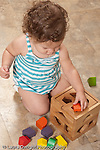 13 month old baby girl at home on floor playing with toy geometric shape sorter trying to fit piece in hole vertical