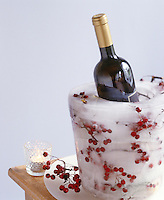 An ice bucket made up of layers of red berries frozen in ice makes an ideal wine cooler and centrepiece