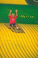 Girl age 7 raising hands riding giant slide at the Minnesota State Fair.  St Paul  Minnesota USA