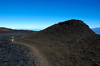 Hiker at the 12000 foot elevation of Mauna Loa volcano Maui and Mauna Kea in the distance Hawaii, USA volcanoes national park the Big Island of Hawaii, USA