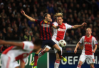F.C Barcelona's Andreas Iniesta (L) jumps for the ball with Ajax's Christian Poulsen (R) during the UEFA Champions League Group H match between Ajax Amsterdam vs F.C. Barcelona at Amsterdam Arena on November 26, 2013 in Amsterdam, Netherlands.. Photo by Paulo Amorim