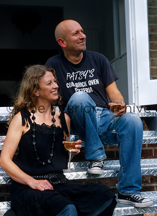 Owners Amanda Sellers and Martin Barrell enjoy a drink on the steps leading down to their patio
