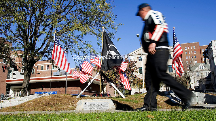 WATERBURY, CT- 11 NOV 2007- 111107JT06- <br /> Navy veteran Jim Berry of Waterbury walks past a POW/MIA memorial display at the Green on Sunday before Veterans Day ceremonies.<br /> Josalee Thrift / Republican-American