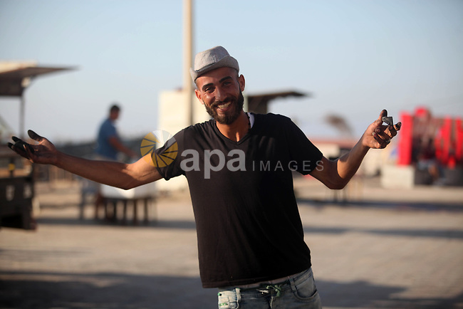 Moawia Ashour, 24, a Palestinian man uses coal to draw on the ground near his street cafe, at the beach of Gaza city, July 30, 2019. Photo by Mahmoud Ajjour