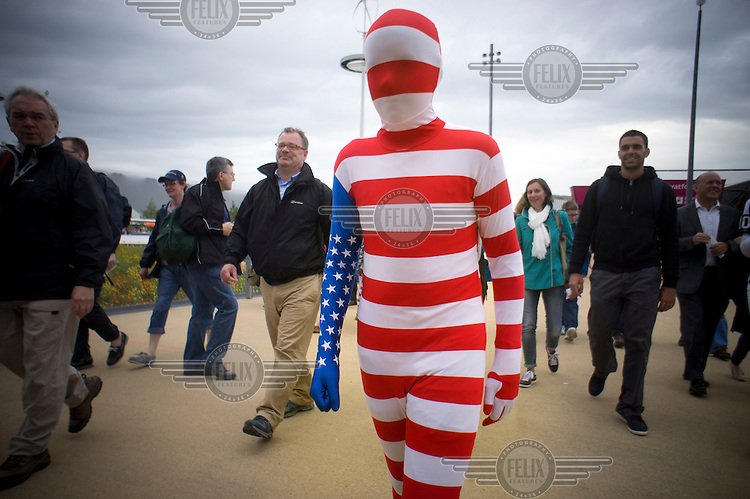 A spectator dressed in an all-encompasing body suit made of an American Flag (Stars and Stripes) makes his way into the Olympic Park in Stratford, East London.