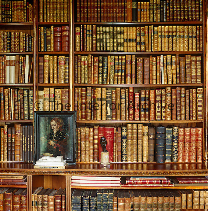 Leatherbound volumes fill the walls of the library and scattered small paintings and sculptures are displayed on the ledge