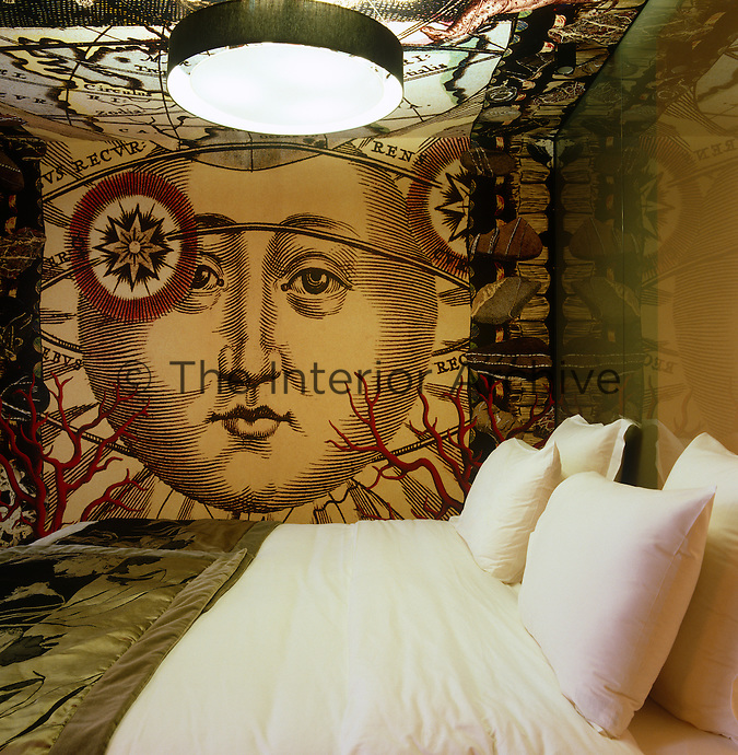 Wallpaper with a large image of the moon and zodiac references covers the walls and ceiling of this compact bedroom