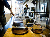 In the lab at the Lake Station water filtration plant, treated water is in the front flask, raw well water in the background.