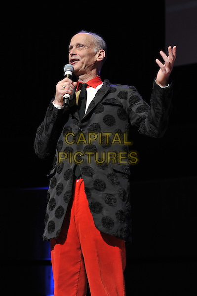 John Waters performing his one man show, 'A John Waters Christmas', Royal Festival Hall, London, England. .5th December 2011.stage concert live gig performance red trousers black polka dot jacket microphone half length hand arm .CAP/MAR.© Martin Harris/Capital Pictures.