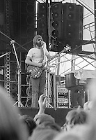 Phil Lesh Playing and Singing. The Grateful Dead in Concert at Dillon Stadium on 31 July 1974. Vertical Shot showing some of the audience, stage, Wall of Sound speaker stacks and the speaker array for piano over his left shoulder. Photograph taken with Nikon FTn Camera and Kodak Tri-X film. Full frame vertical.