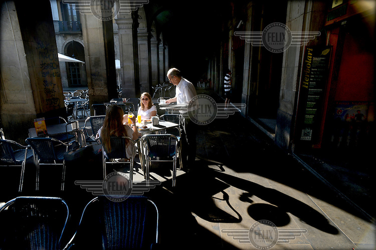 A waiter serves breakfast to tourists sitting in an arcade in the Placa Reial. /Felix Features