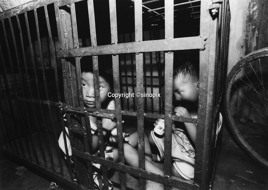 Children, aged 3 and 5, are kept in a cage in a village house belonging to their uncle. The children's parents are both in prison and the uncle is too poor to afford child care for the children.<br />