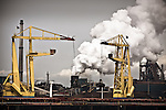 Two cranes offload coal from a massive ship to fuel the Hoogovens in Ijmuiden, the Netherlands.
