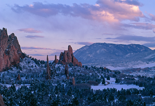 A winter sunset surrounds the Garden of the Gods park with Cheyenne Mountain in the distance, Colorado Springs, CO