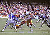 Washington Redskins left tackle Joe Jacoby (66) leads running back John Riggins (44) through a hole in the Detroit Lions defense during a game at RFK Stadium in Washington, DC on October 13, 1985.  Lions free safety William Graham (33) and right outside linebacker Angelo King (92) defend on the play.  The Redskins won the game 24 - 3.<br /> Credit: Arnie Sachs / CNP