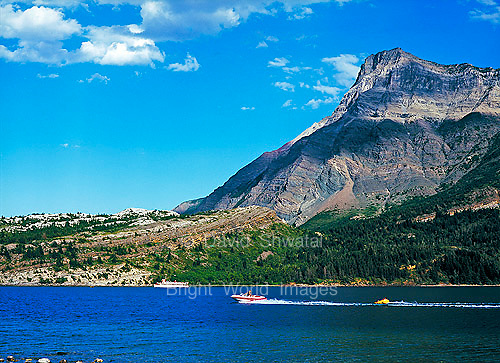 mountains and blue sky above speed boat tube and ferry on blue Upper Waterton Lake in Waterton Lakes International Peace Park Alberta Canada
