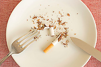 Torn up cigarette on plate with knife and fork