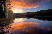 Bright colors and skies are reflected in the glassy water of Kolob Reservoir at sunset near Zion National Park, Utah
