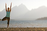 A young woman practices yoga on the shore of Jackson Lake in Grand Teton National Park, Jackson Hole, Wyoming (selective focus).