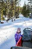 USA, Oregon, Bend, a young girl examines the cargo bed while waiting to depart on her sled dog ride at Mt. Bachelor