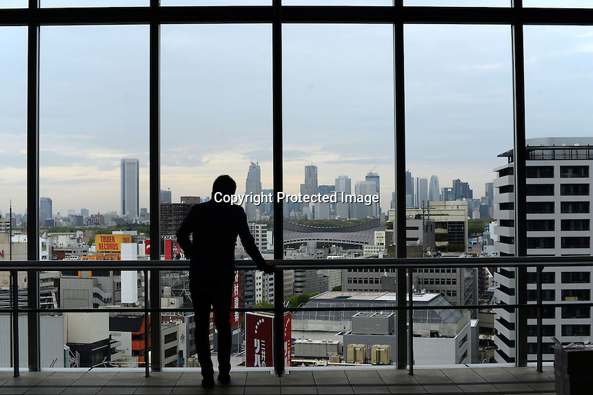 A businessmen looks through a window at Shibuya Hikarie, a new skyscraper in the Shibuya district of Central Tokyo, Japan.<br /> Apr-2014