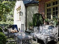 The outdoor sofa and ottomans were painted grey and upholstered in taupe to blend with the stone terrace