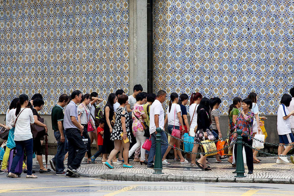 Pedestrians walking near an elaborately tiled wall.<br />