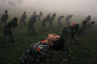 Maoist rebel soldiers of the People's Liberation Army stretch during their early morning physical training at a cantonment in Nawalparasi, Nepal on 29 October 2007. The PLA have been in UN monitored camps since a peace deal between the Maoists and Nepal's other political parties was agreed to in the Spring of 2006