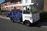 Traditional milk float making deliveries along a street, Ipswich, Suffolk, England
