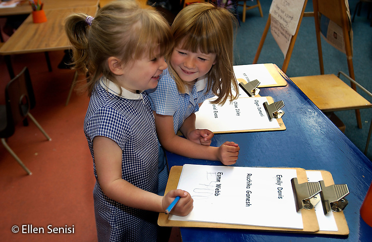 MR / Abingdon, Oxfordshire, England.Thomas Reade Primary School.Foundation Class for ages 3-5 .Girls talk as they sign in on clipboard at beginning of school day.  Daily name recognition and writing reinforces this basic skill..(Ages 3-4 attend this class half-day, age 5 attends full-day).©Ellen B. Senisi