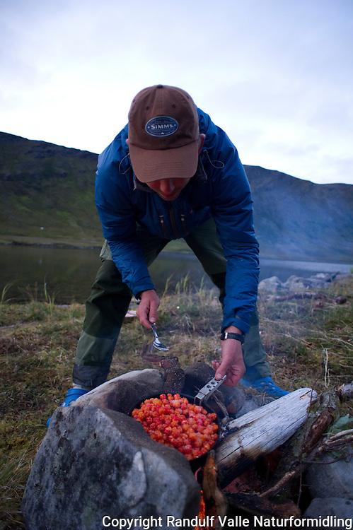 Mann varmer molter i steikepanne på bålet. ---- Man cooking cloudberries in frying pan.