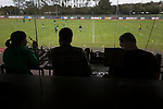 The PA announcer and journalists watching the players warming-up as Guernsey take on Corinthian-Casuals in a Isthmian League Division One South match at Footes Lane. Formed in 2011, Guernsey FC are a community club located in St. Peter Port on the island of Guernsey and were promoted to the Isthmian League Division One South in 2013. The visitors from Kingston upon Thames won the fixture by 1-0, watched by a crowd of 614 spectators.