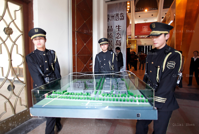 Security guards carry a models of a residential development at a real estate fair in Shanghai, China on 15 March, 2009. For the past decade, Shanghai has underwent the largest reconstruction in recorded history, over 20 million square meters of land, approximately a third of Manhattan, were developed between year 200 and 2005 alone. Despite that however, housing prices have seen a rapid increase, putting the prospect of owning a decent sized home out of the reach of ordinary Chinese citizens, especially middle to low income families.