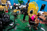 A member of a samba school arranges carnival costumes (fantasias) inside the workshop in Rio de Janeiro, Brazil, 15 February 2012. The carnival preparations start early in July or August, some 7-8 months before the main samba schools parade at the sambodrome. Samba schools hire teams of professional designers and artists who, according to the original theme selected by the school directors and then featured by the school during the parade, create allegorical floats, costumes, sculptures, music, choreography and the entire school show. However, the most of the everyday work in the carnival hangars is performed by unknown but fully dedicated samba schools members.