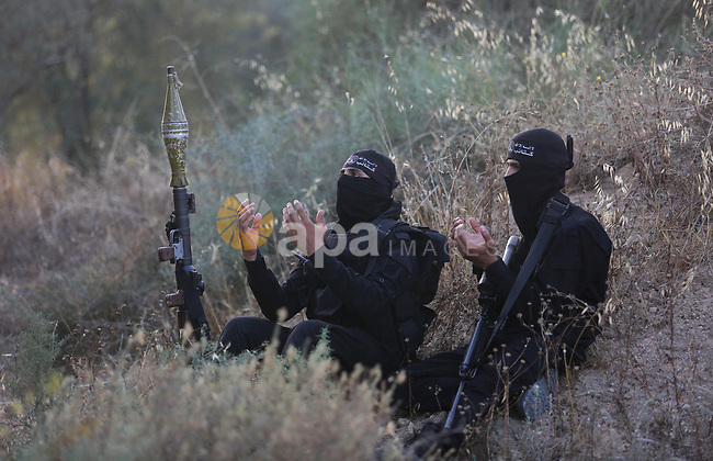 Palestinian militants pray at the border in the east of Gaza city on the Muslim holy fasting month of Ramadan on May 24, 2018. Ramadan is sacred to Muslims because it is during that month that tradition says the Koran was revealed to the Prophet Mohammed. The fast is one of the five main religious obligations under Islam. More than 1.5 billion Muslims around the world will mark the month, during which believers abstain from eating, drinking, smoking and having sex from dawn until sunset. Photo by Ashraf Amra