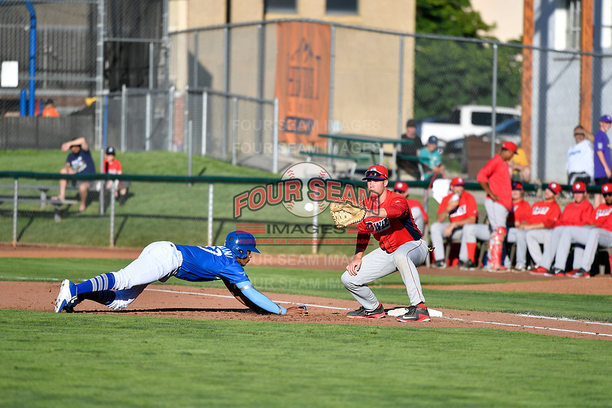 Cristian Santana (27) of the Ogden Raptors dives back to first base while Orem Owlz first baseman David MacKinnon (19) takes the throw in Pioneer League action at Lindquist Field on June 22, 2017 in Ogden, Utah. The Owlz defeated the Raptors 13-8.  (Stephen Smith/Four Seam Images)