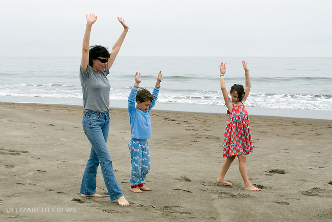Stinson Beach, CA Aunt and nephew, six, and niece, eight trying to do hand stands during beach vacation MR