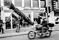 Switzerland. Canton of Geneva. Geneva. Air France shop with drawing of the Concorde plane. Four men are installing a Christmas tree as  winter decoration on the Mont-Blanc road. A biker with helmet on a speedy motorbike.  25.11.99 © 1999 Didier Ruef
